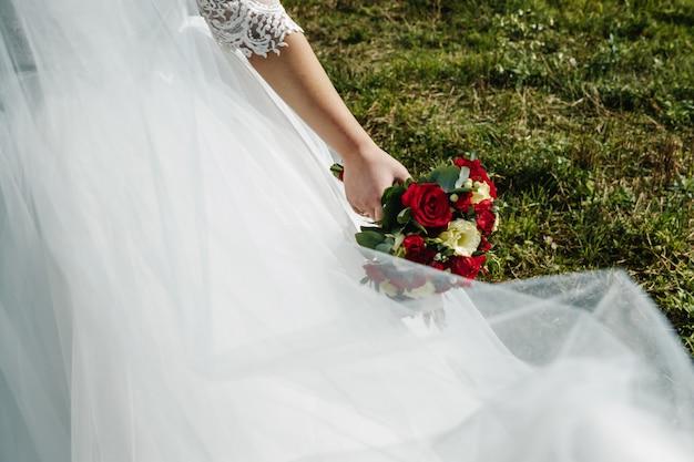 Zamyka up panna młoda trzyma ślubnego bukiet z czerwonymi i białymi różami.