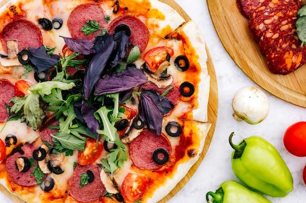 Zamyka up pepperoni pizza z oliwną pomidor pieczarką i ziele