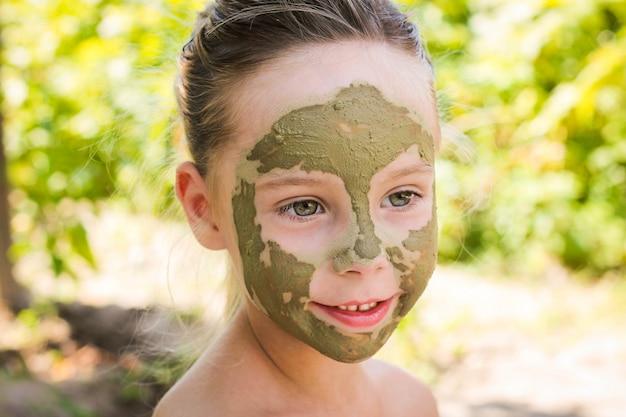 Zamyka up piękna dziewczyna z twarzową gliny maską