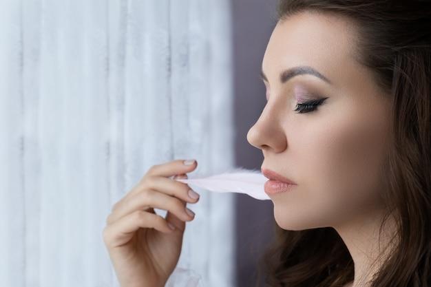 Zamyka up piękna młoda kobieta dotyka jej kurczątka z białym piórkiem.