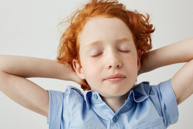 Zamyka up piękna śpiąca imbirowa chłopiec trzyma ręki za głową z zamkniętymi oczami z kędzierzawym włosy i piegami