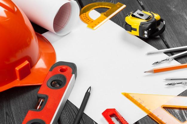 Zamyka up pomarańczowy hardhat i naprawia narzędzia