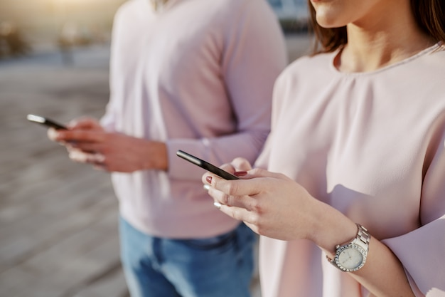 Zamyka up potomstwo para używa mądrze telefony outdoors