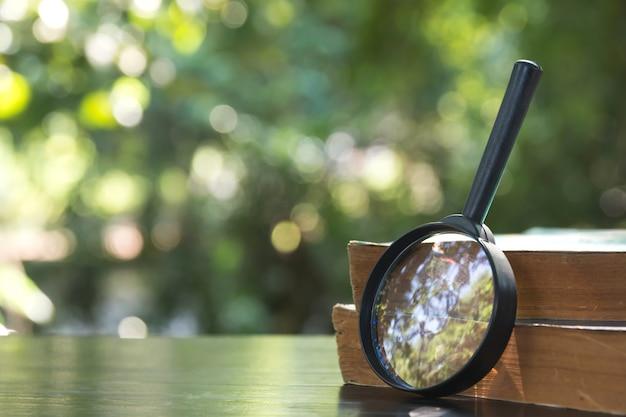 Zamyka up powiększać - szkło z starymi książkami na drewnianym stołu i natury tle.