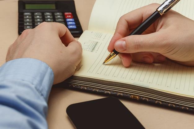 Zamyka up przypadkowy mężczyzna writing na papierowym notatniku lub starym dzienniczku