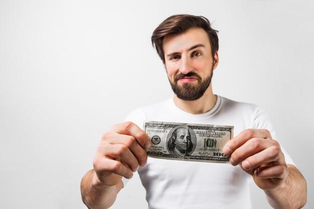 Zamyka up przystojna brunetka mężczyzna stoi blisko białej ściany i trzyma dolarowego rachunek. pokazuje, że ma sto dolarów. facet wygląda na szczęśliwego. wytnij widok. pojedynczo na białej ścianie.