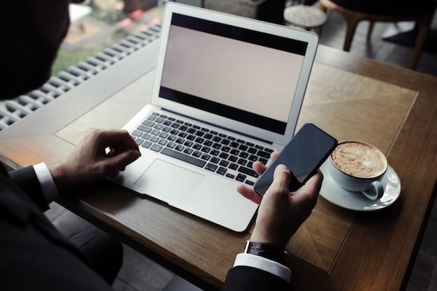 Zamyka up przystojny biznesmen, pracuje na laptopie w restauraci