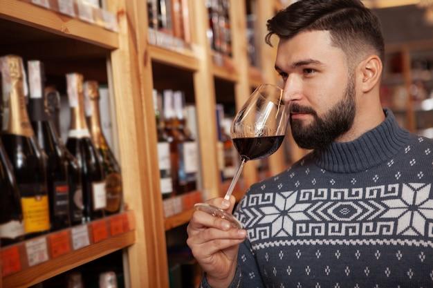 Zamyka up przystojny brodaty mężczyzna wącha starzenia się czerwone wino w szkle, robi zakupy przy sklepem z winem