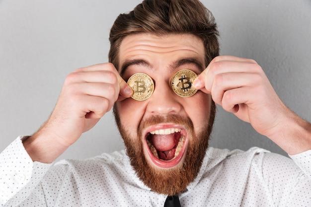 Zamyka up radosny biznesmen z bitcoins w jego oczach