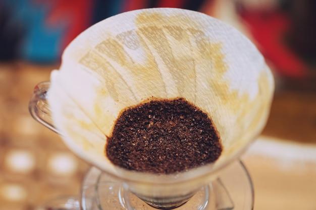 Zamyka up ręka kapie kawę, kawa mlejąca z filtrem