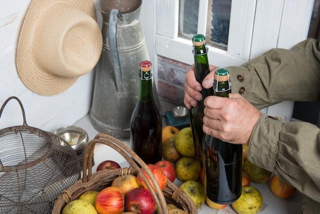Zamyka up ręka mężczyzna z butelką cydr i jabłka