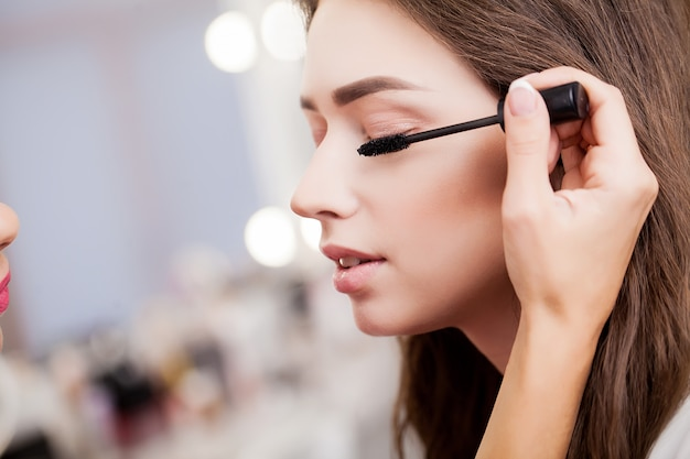 Zamyka up ręka stosuje eyeshadow na żeńskiej powiece azjatykcia kobieta.