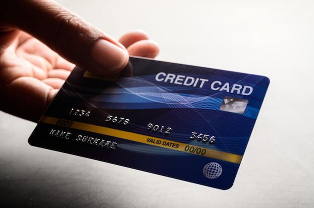 Zamyka up ręka trzyma kredytową kartę