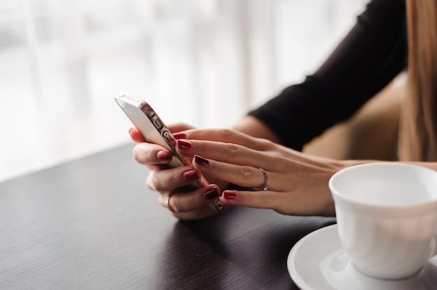 Zamyka up ręki kobieta używa jej telefon komórkowego w restauraci, kawiarnia