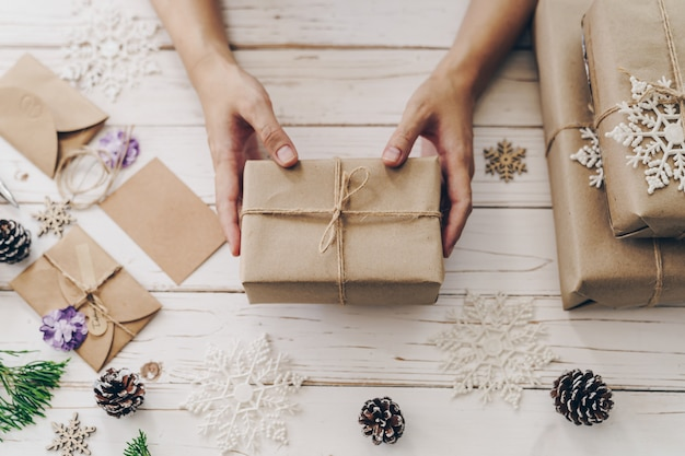 Zamyka up ręki kobiety teraźniejszości prezenta pudełko na drewnianym stole z xmas dekoracją.