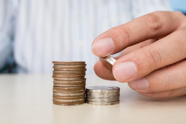 Zamyka up ręki mienie i kładzenie moneta na górę sterty monety