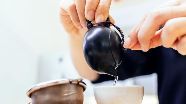 Zamyka up ręki nalewa chińską zieloną herbatę od ceramicznego czajnika
