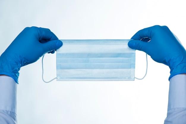 Zamyka up ręki w gumowych rękawiczkach trzyma chirurgicznie maskę. pojedynczo na białym tle. covid 19 koronawirus