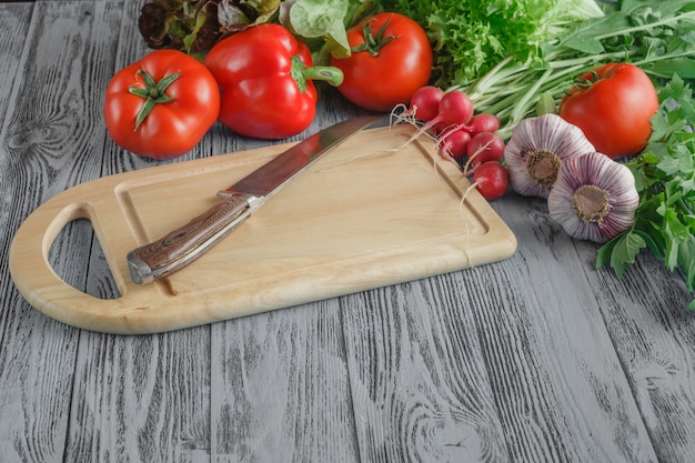 Zamyka up różnorodni warzywa na drewnianej tnącej desce