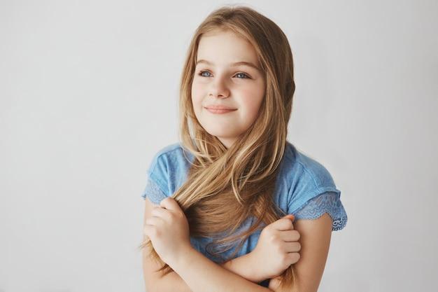 Zamyka up rozochocona mała blondynki dziewczyna z niebieskimi oczami trzyma włosy z rękami, patrzeje na boku z szczęśliwym i zrelaksowanym wyrażeniem.
