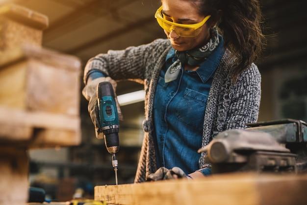 Zamyka up rozochocona pracowita krótkiego włosy kobieta pracuje z elektrycznym świderem w tkaninowym warsztacie