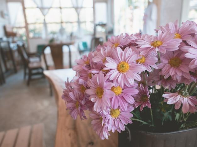 Zamyka up różowi kwiaty na drewnianym stole w kawiarni