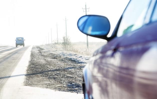 Zamyka up samochód na drodze zakrywającym hoarfrost