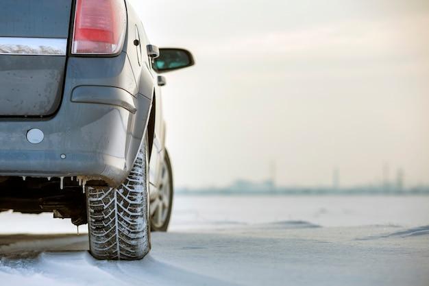 Zamyka up samochodowa opona parkująca na śnieżnej drodze na zima dniu. koncepcja transportu i bezpieczeństwa.