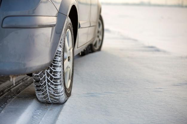 Zamyka up samochodowa opona parkująca na śnieżnej drodze na zima dniu