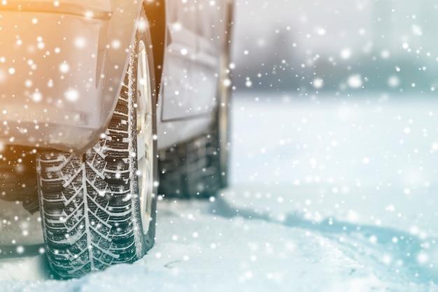 Zamyka up samochodowych kół gumowe opony w głębokiej zimy śniegu drodze