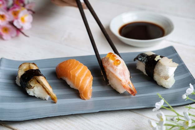 Zamyka up sashimi suszi ustawiający z kumberlandem sojowym na białym drewnianym stole