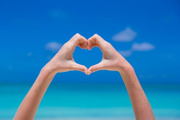 Zamyka up serce robić żeńskimi rękami w plaży