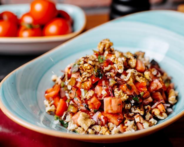 Zamyka up siekająca świeża sałatka z pomidorami pieprzy ziele i orzechów włoskich w talerzu