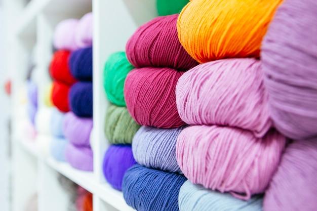 Zamyka up składowe kolorowe przędze wełniane organizowane według koloru na półce
