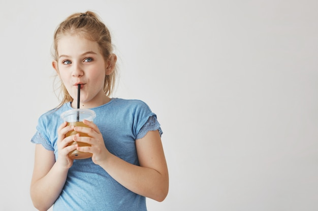 Zamyka up śliczna dziewczyna trzyma szklankę mleko w rękach z lekkim włosy w ogon fryzurze, pije przez słomy i patrzeje na boku z śmieszną twarzą.