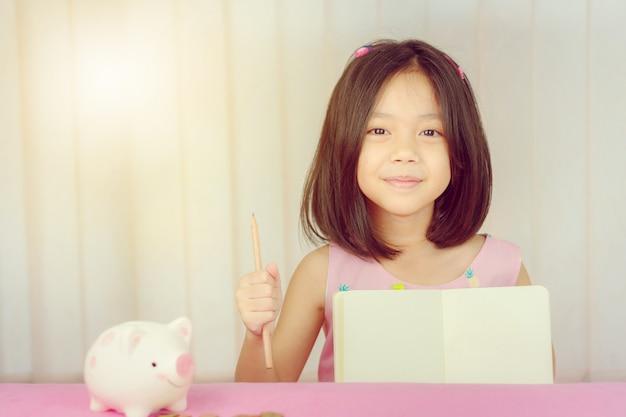 Zamyka up śliczna mała dziewczynka z książkowym ołówkiem i prosiątko bankiem
