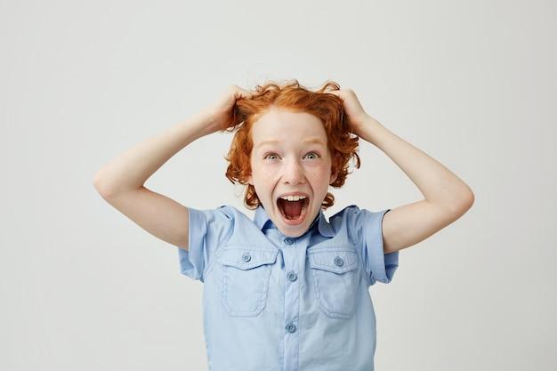 Zamyka up śmieszny chłopiec z czerwonym włosy i piegami ciągnie włosy z rękami, krzyczy z zdziwionym wyrażeniem