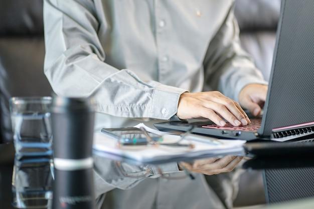 Zamyka up starszy biznesmen pracuje przy biurem.