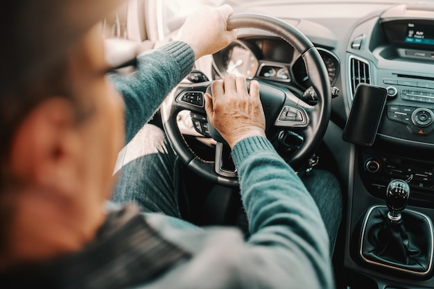 Zamyka up starszy mężczyzna jedzie jego samochód.