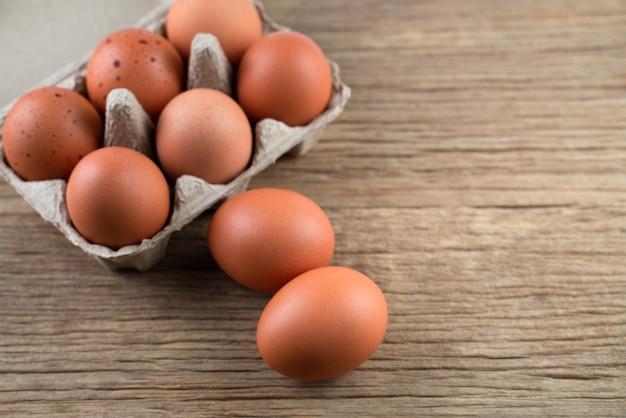 Zamyka up surowi kurczaków jajka w jajecznym pudełku, żywność organiczna od naturalnego na nieociosanym drewno stole