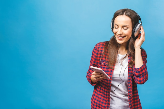 Zamyka up szczęśliwa młoda dama stoi przy użyciu telefonu słuchania muzyki w słuchawkach