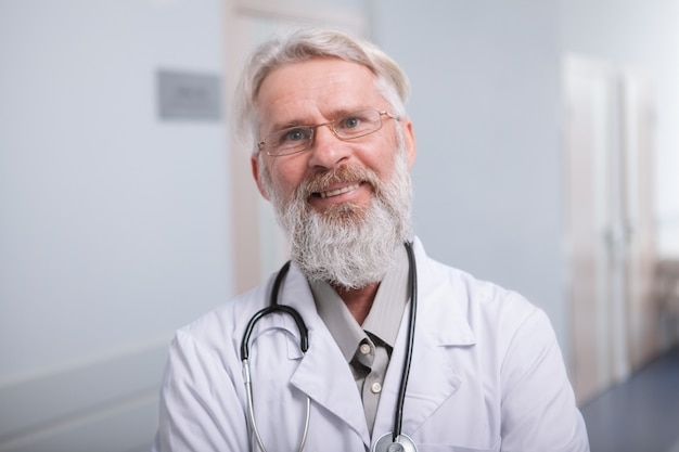 Zamyka up szczęśliwy starszy brodaty doktorski ono uśmiecha się kamera, pracuje przy kliniką