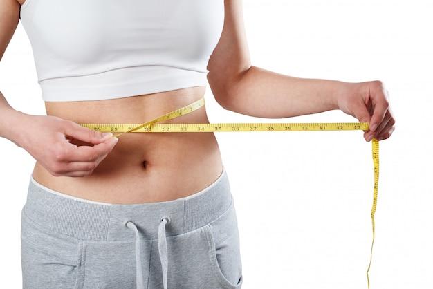 Zamyka up szczupła kobieta mierzy jej talii rozmiar z taśmy miarą.
