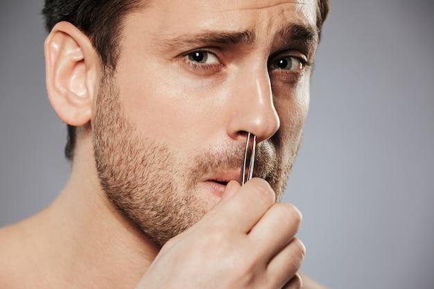 Zamyka up terrifoed mężczyzna usuwa nosa włosy