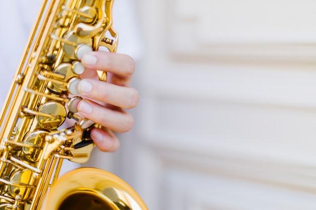 Zamyka up trzymającego saksofon z zamazanym tłem