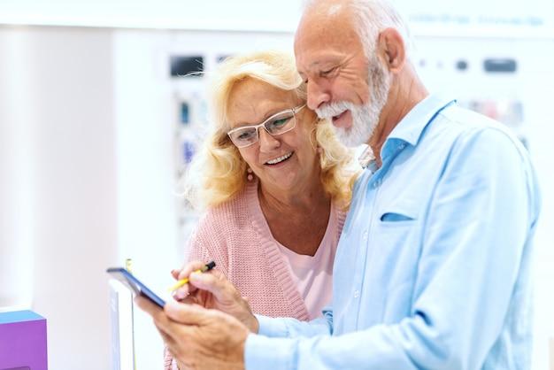 Zamyka up uśmiechnięta stara para próbuje out pastylkę podczas gdy stojący w technika sklepie.