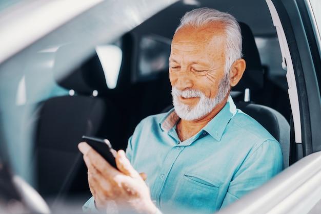 Zamyka up uśmiechnięty brodaty senior używa mądrze telefon dla pisać lub czytać wiadomość z ręką na rozpieczętowanym okno podczas gdy siedzący w samochodzie.