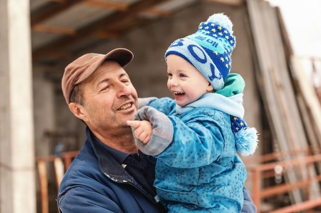 Zamyka up uśmiechnięty dziadek trzyma jego wnuka na zimnej pogodzie. obaj ubrani w ciepłe zimowe ubrania.