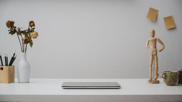 Zamyka up workspace z laptopem, ołówkami, drewnianą postacią, suchej róż wazy i filiżanką na białym biurku z biel ścianą