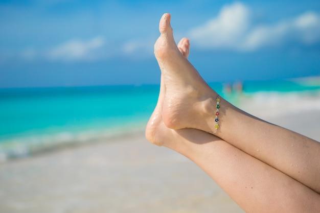 Zamyka up żeńscy cieki na białej piaskowatej plaży
